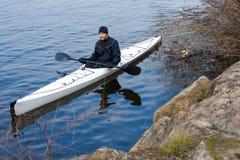 一艘白色皮船的一个人在城市riverbank09附近 库存图片