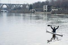 一艘白色皮船的一个人在城市riverbank10附近 免版税库存照片