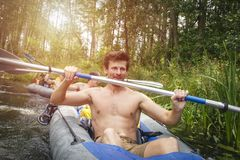 一艘皮船的一个年轻运动的人有桨的 乘独木舟在夏季期间的河 免版税库存图片