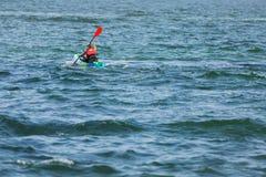 一艘皮船的人有桨的,游泳在公海,水上运动,生活方式 库存图片