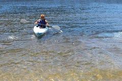 一艘皮船的十几岁的男孩在一个湖在夏天 免版税库存照片