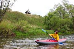 一艘皮船的女孩在河和一个木教会银行的 图库摄影