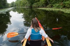 一艘皮船的女孩在河 免版税库存照片