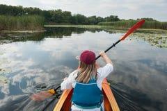 一艘皮船的女孩在河 免版税库存图片