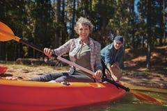 一艘皮船的愉快的资深妇女在湖 免版税库存照片