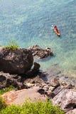一艘皮船的游人在大岩石前面在热带 库存照片