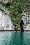一艘皮船的游人在大岩石前面 库存图片