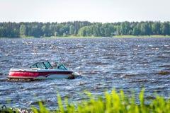 一艘红白的汽艇晃动在湖的波浪 库存照片