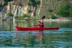 一艘红色皮船的人在岸附近 库存图片
