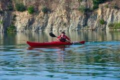一艘红色皮船的人在shore02附近 库存照片