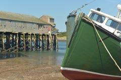 一艘绿色捕鱼拖网渔船的弓处于低潮中 库存图片
