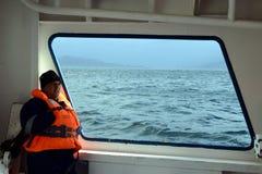 一艘船的甲板的一位水手在合恩角附近的 库存照片