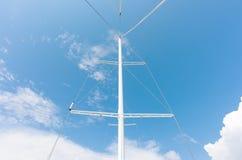 一艘船的白合金帆柱没有风帆的在明亮的天空的背景 库存照片