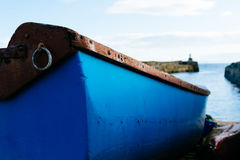 一艘蓝色划艇的近景有的在焦点灯塔外面 免版税库存照片