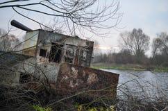 一艘被毁坏的驳船在河岸停泊了 免版税图库摄影