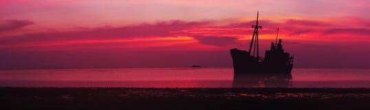 一艘被碰撞的船的剪影在海 在海运日落 全景 库存照片