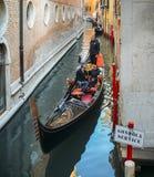 一艘长平底船的游人在一条狭窄的运河在威尼斯,意大利的历史的中心 免版税库存照片