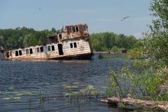 一艘驳船的凹下去的房子在普里皮亚季河的中部,切尔诺贝利,乌克兰 免版税库存照片