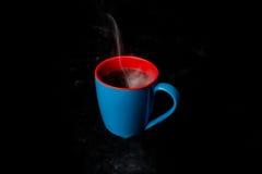 一蓝色杯热的通入蒸汽的咖啡黑色背景 图库摄影