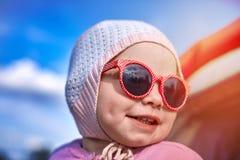 一被编织的帽子和红色太阳镜微笑的小两岁的女孩 免版税库存照片