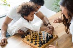 一起下棋的愉快的家庭在家 库存照片
