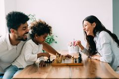 一起下棋的愉快的家庭在家 免版税图库摄影