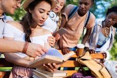 一起不同种族的学生阅读书在长凳在公园 库存照片