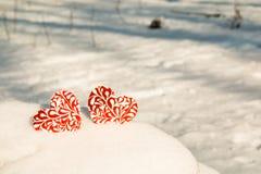 一起两红色心脏在雪 库存图片