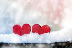 一起两美丽的浪漫葡萄酒红色心脏在白色雪冬天背景 爱和圣情人节概念 免版税图库摄影