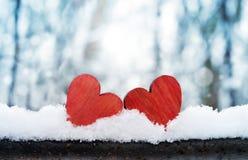 一起两美丽的浪漫葡萄酒红色心脏在白色雪冬天背景 爱和圣情人节概念 免版税库存图片