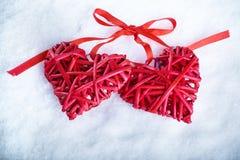 一起两美丽的浪漫葡萄酒红色心脏在白色雪冬天背景 爱和圣情人节概念 免版税库存照片