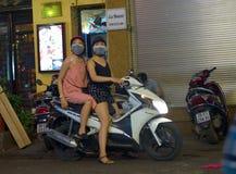 一起乘坐在一辆自行车的女孩在夜河内 库存照片