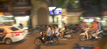 一起乘坐在一辆自行车的家庭在夜河内 图库摄影