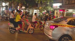 一起乘坐在一辆自行车的家庭在夜河内 免版税库存图片