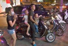 一起乘坐在一辆自行车的家庭在夜河内 库存照片