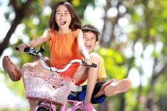 一起乘坐自行车的孩子 库存图片