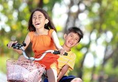 一起乘坐自行车的孩子 免版税库存照片