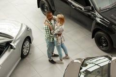 一起买新的汽车的愉快的夫妇在经销权 免版税图库摄影