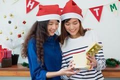 一起亚洲女朋友开放金礼物盒在圣诞节和新年党,假日庆祝季节事件 免版税库存图片