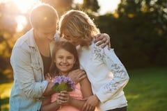 一起享受一个晴天的微笑的年轻家庭户外 免版税图库摄影