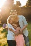 一起享受一个晴天的愉快的年轻家庭外面 免版税库存照片