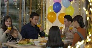 一起享受圣诞晚餐的愉快的亚洲家庭在家 股票录像