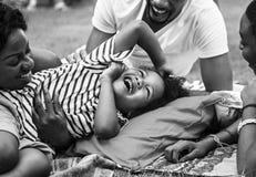 一起享受夏天的黑家庭在后院灰色极谱 免版税库存照片