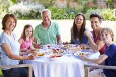一起享受室外膳食的多一代家庭 免版税图库摄影