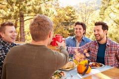 一起享受室外膳食的小组快乐男性朋友 库存照片
