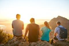 一起享受日出的朋友在自然远足 免版税库存图片
