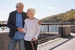 一起享受消遣的被迷住的夫妇在河附近 免版税库存照片