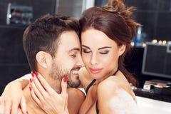 一起享受蜜月的愉快的年轻夫妇在极可意浴缸 库存图片
