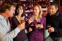 一起享受饮料的组朋友在棒 库存图片