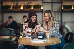 一起享用咖啡在咖啡馆和使用电话的朋友 免版税库存照片
